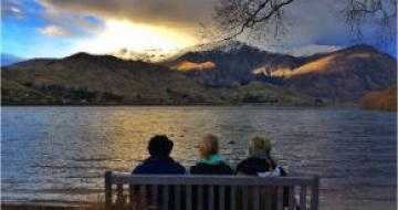 Photo of friends sitting in front of a lake in New Zealand