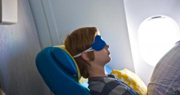 Young man asleep on a plane