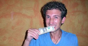 Man biting a $1 note