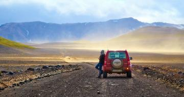 Woman standing next to car in Iceland Desert