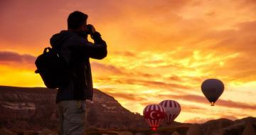 Man taking a photo of hot air balloons at sunrise in Turkey